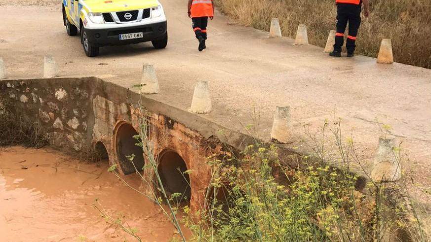 Miembros de protección civil revisan un cauce repleto de agua