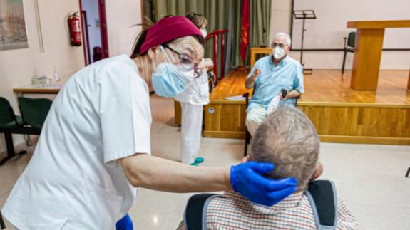 La trabajadora de un geriátrico asiste a un anciano. Consejería de Política Social