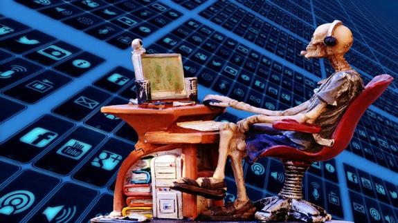 Figura de esqueleto consultando un ordenador
