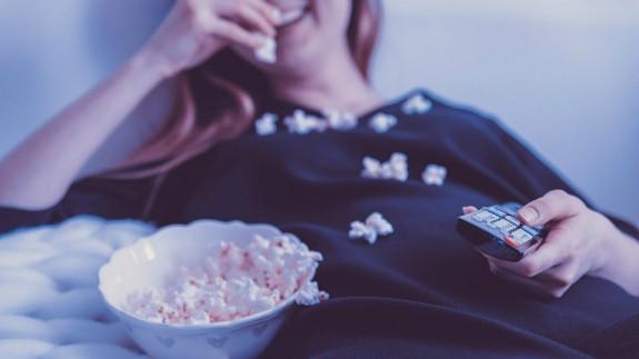 Mujer con mando del televisor comiendo palomitas de maíz