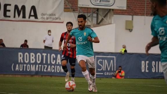 El murcianista Saura, exjugador del Yeclano, conduce el balón durante el partido