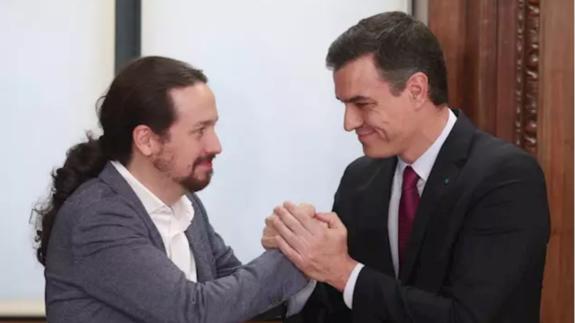 Pablo Iglesias y Pedro Sánchez estrechándose las manos tras alcanzar un acuerdo de gobierno