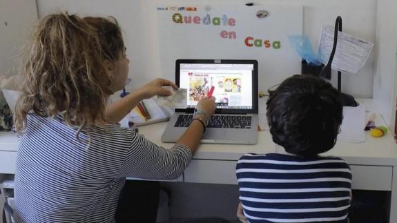 Una madre junto a su hijo en una clase telemática