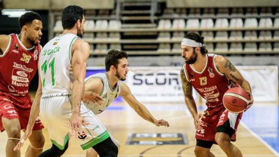 Diego Kapelan, con el balón, defendido por dos jugadores rivales