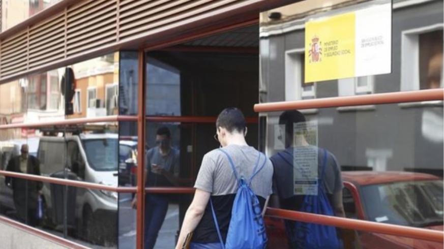 Un joven frente a una oficina de empleo
