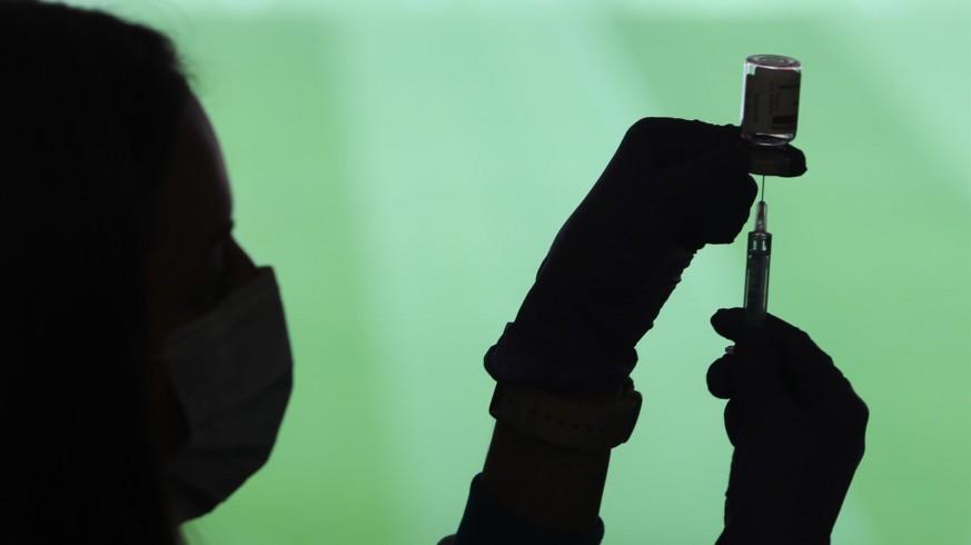 Profesional sanitaria sostiene una jeringuilla y un vial con la vacuna del Covid-19