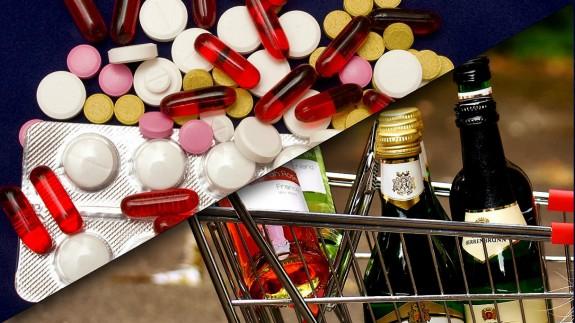 Medicamentos y carro de supermercado con botellas de alcohol