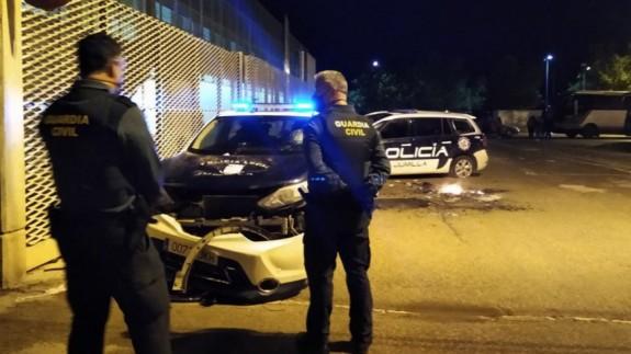 Agentes de la Guardia Civil contemplan los destrozos de dos vehículos policiales en Jumilla. ORM