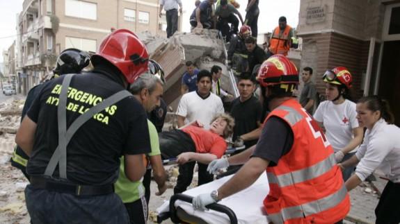 Bomberos y sanitarios atienden a una mujer rescatada de la ruinas de un edificio. JUAN CABALLERO