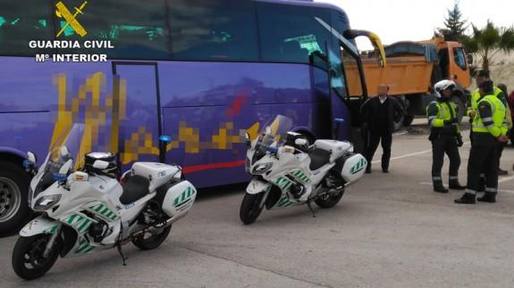 El conductor de autobús junto a la patrulla que le interceptó
