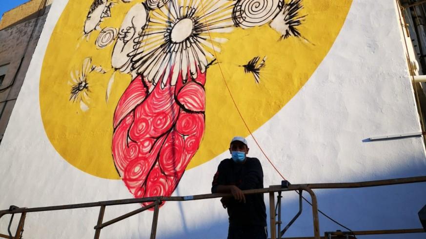 El artista Murfy, junto a su nuevo mural en Alhama